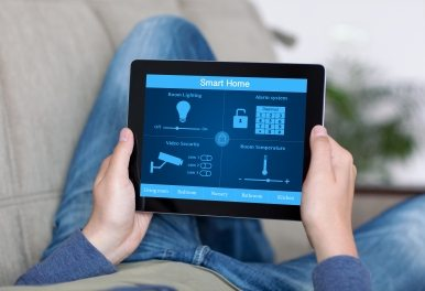 man using tablet to control house security systems